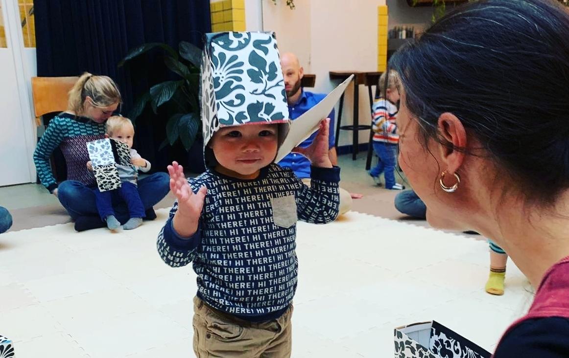 Een kind ontdekt de mogelijkheden van materialen in een Muziek op Schootbijeenkomst.