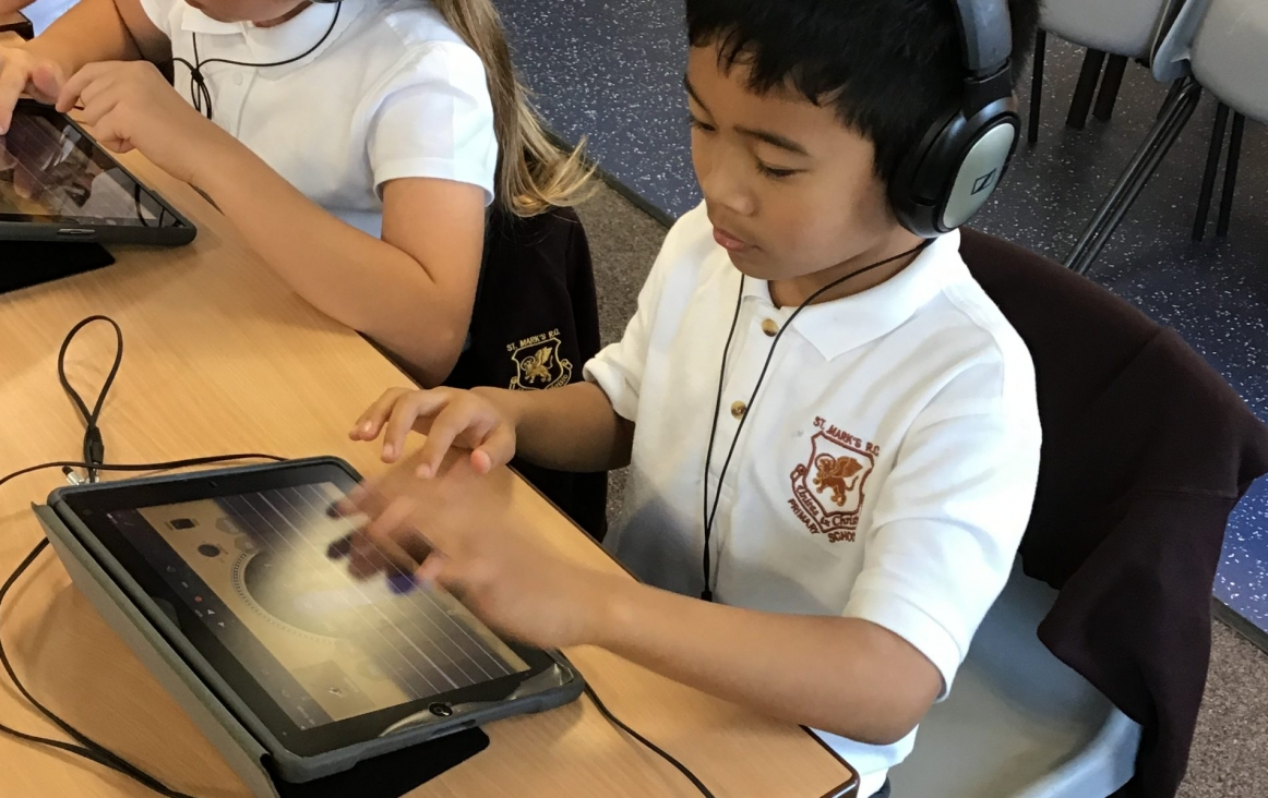 Jongen met iPad maakt muziek