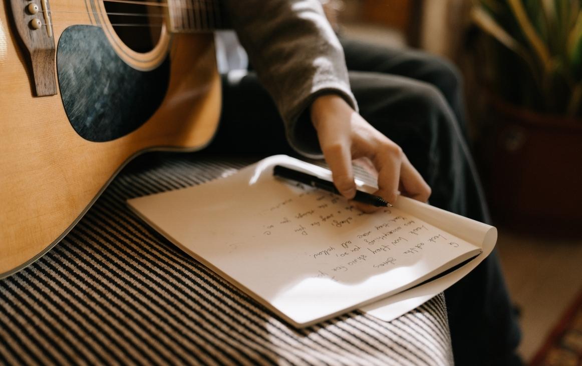 Een liedje schrijven met de gitaar bij de hand. Bron: Pexels Cottonbro