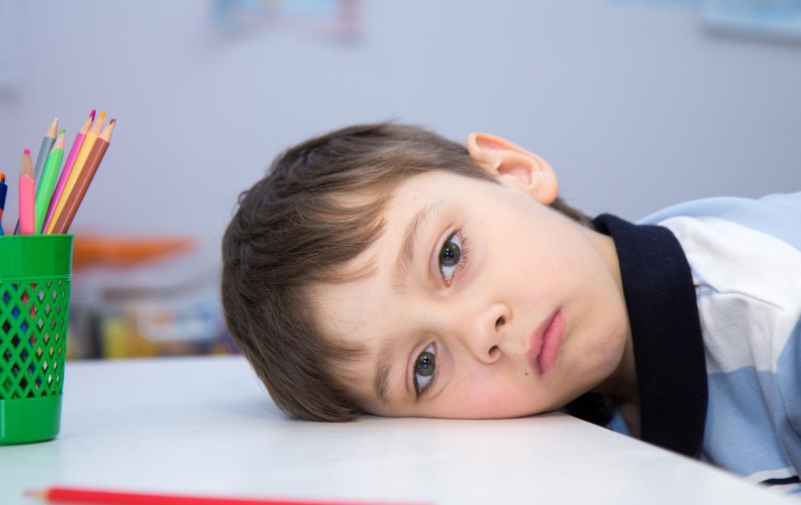 Foto van een balend kind met het hoofd op de lessenaar. Foto Shutterstock