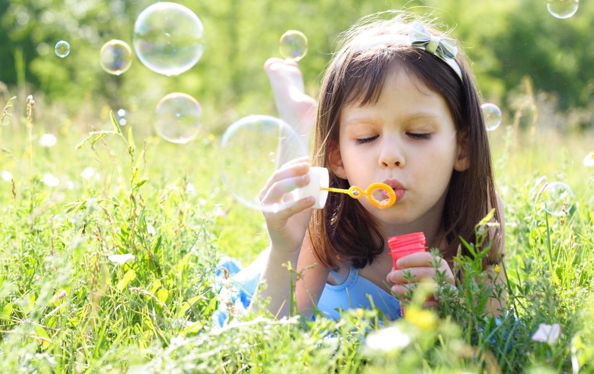 Meisje flierefluitend aan het bellenblazen. Foto Shutterstock 57114478