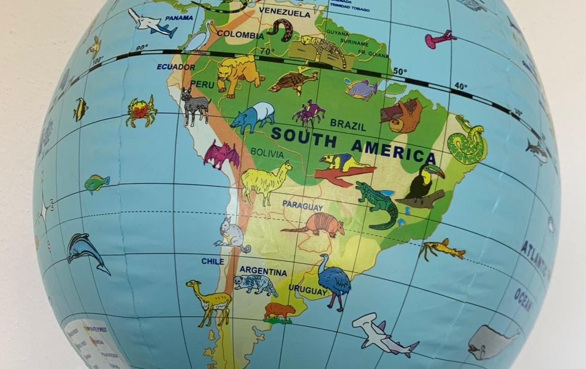 Zuid-Amerika op een wereldbol met grappige dierentekeningen erbij