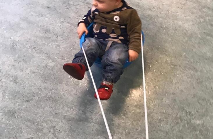 Sleetje rijden in een teiltje op het vloerkleed