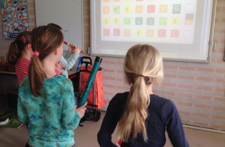Kinderen met boomwhackers en blokfluit spelen een partituur van Muziek in School. Foto Helga Boekestijn